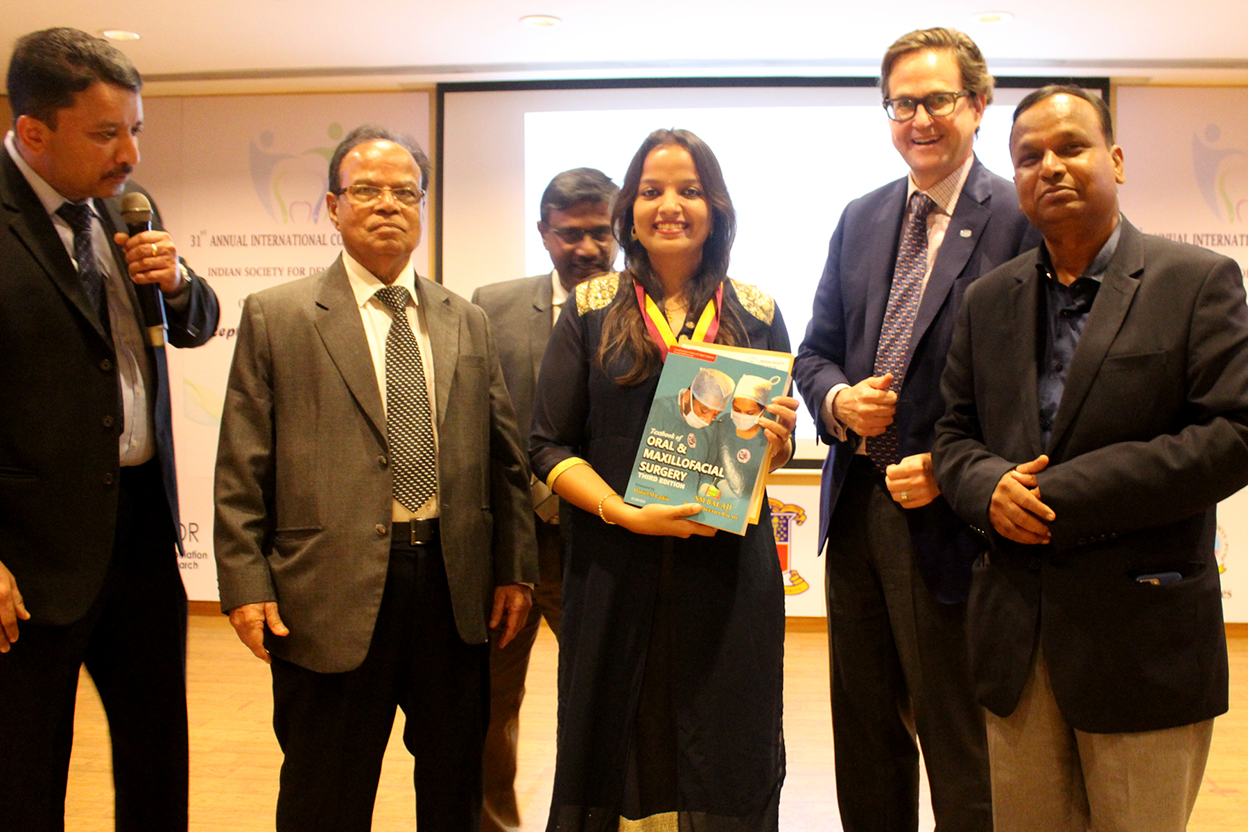 A top ranker being presented with Dr SM Balaji's Textbook of Oral and Maxillofacial Surgery